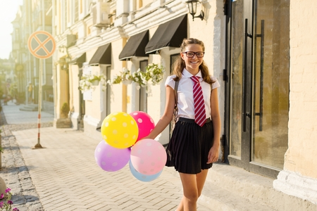 Girl teenager high school student with balloons, in school uniform with glasses goes along the city street. Start of classes.