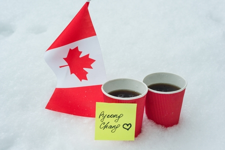 Kyiv UA, 21-12-2017, 2018 Winter Olympic Games with kinds of sport in PyeongChang, Republic of Korea, The flag of the Canada team, two cups of fans with coffee and a sticker - PyeongChang with love.