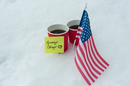 2018 Winter  Games with kinds of sport in PyeongChang, Republic of Korea, the flag of the USA team, two cups of fans with coffee and a sticker - PyeongChang with love. Banque d'images