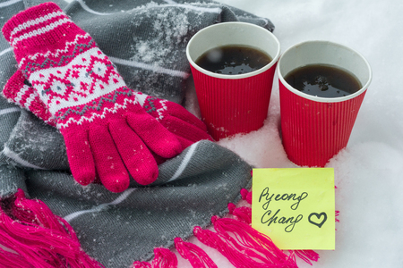 Snow-covered scarf and gloves on snow, two cups of fans with coffee and a sticker - PyeongChang with love.