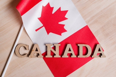 Flag of Canada, the word Canada in wooden abstract letters, wooden background Standard-Bild