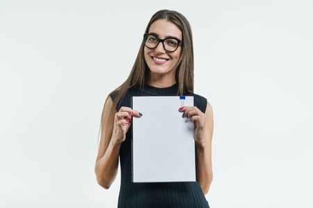 Positive smiling businesswoman showing a clean white document with copy space. White background