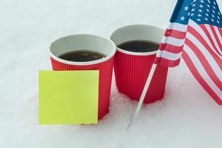 The flag of the USA team, two cups of coffee in snow with a clean paper sticker - place for your test, information. Banque d'images