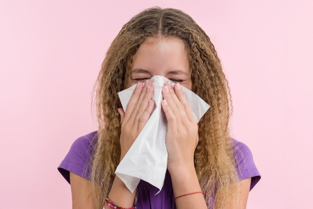 Cute young girl child sneezing in a tissue blowing his runny nose Stock Photo
