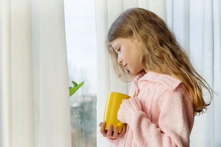 Girl child 7 years old blonde with long wavy hair in a warm knitted sweater holds a cup of tea and looks in the window.