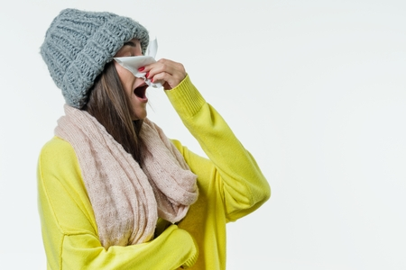 Woman in a sweater, knitted hat, scarf sneezes with a handkerchief. Season of the common cold, viruses, rhinitis. White background, copy space