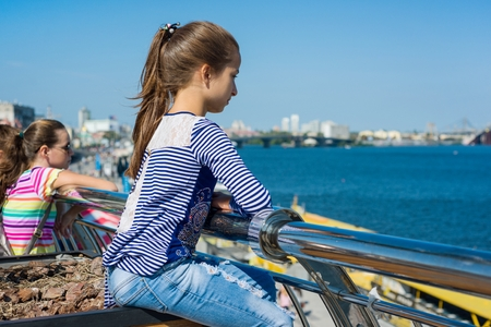 Portrait of a 10 year old girl in a profile. Background of a river in a modern city, blue sky