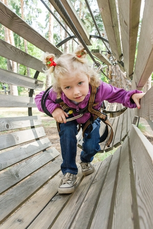 The girl is 4 years old in adventure climbing high wire park, active lifestyle of children