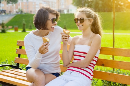 Holiday with the family. Happy young mother and cute daughter teenager in city park eating ice cream, talking and laughing.