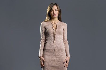 Beauty fashion model girl wearing stylish knitted dress. Sexy woman portrait with perfect makeup.