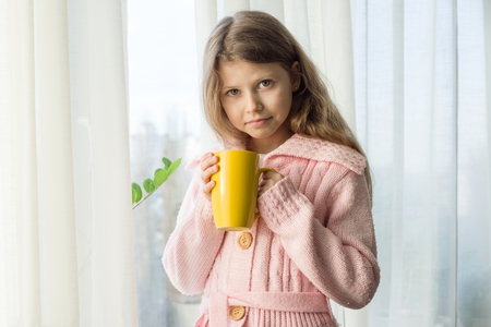 Girl child 7 years old blonde with long wavy hair in a warm knitted sweater holds a cup of tea and looks in the window