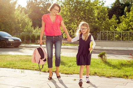 Mother and daughter student walking to school. Back to school