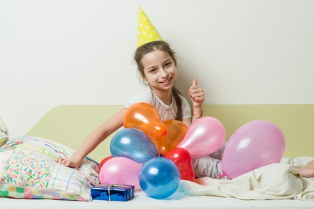 The teenage girls birthday is 10-11 years old. A girl in a festive hat lies with a gift on the bed in a childrens room, background balloons