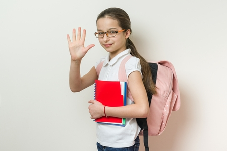 Portrait of a smiling schoolgirl 10 years old with glasses, with a backpack, notebooks giving high five to camera, background bright wall in school Stock Photo
