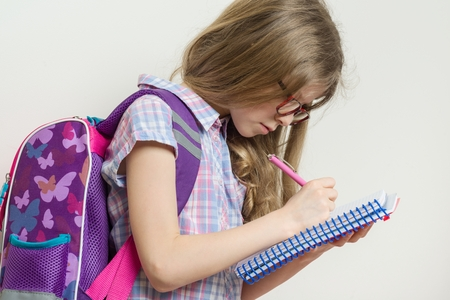 Young schoolgirl in glasses and with a backpack writes in a school notebook. Background bright wall in school