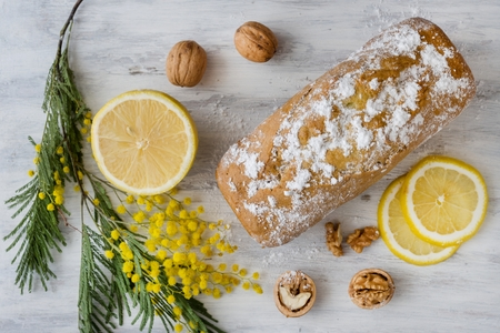 Lemon cake with nuts on a wooden white surface, a twig of mimosa flowers.