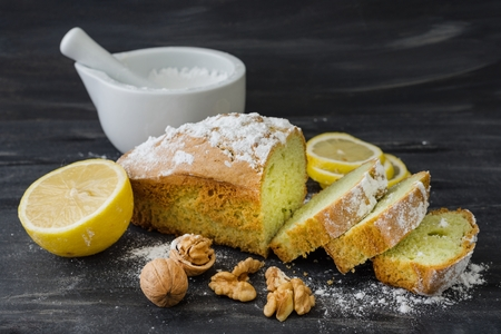 Mint cake on black surface with lemon, nuts, powdered sugar.
