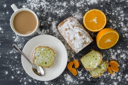 Mint cake sprinkled with powdered sugar on dark surface with fresh oranges mandarins Stock Photo