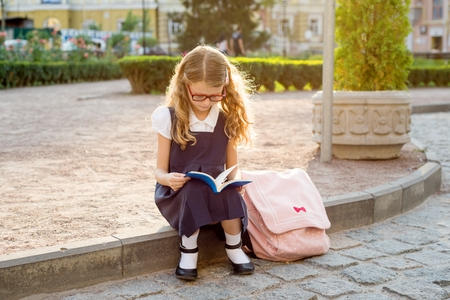 Young schoolgirl reading a book. Urban style background.
