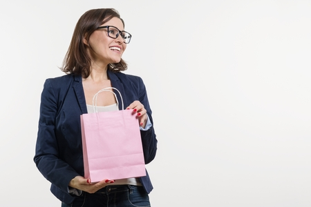 Beautiful middle aged woman opening a shopping bag, white background
