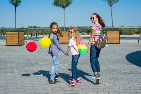 Back view of children schoolgirls holding hands walk together on urban road outdoors background.