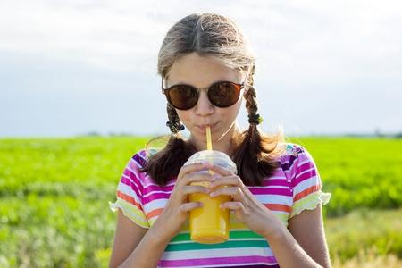 Happy teen girl drinking orange juice at hot summer day. Outdoor