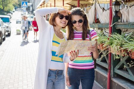 Mom and daughter tourist looking at the map on the street of european city, travel to Europe