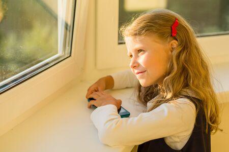 Beautiful cute little girl dressed in school uniform looking out the window. Stock Photo