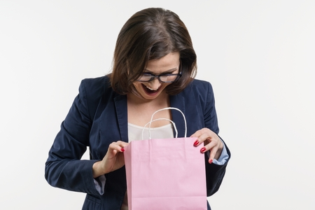 Surprised adult woman looking shopping bag, white background, Stock Photo