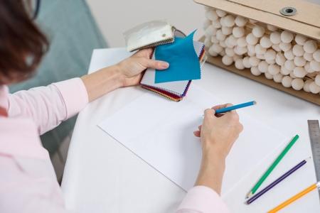 Workplace interior designer. Interior designer draws at desk in office with pencil. Stock Photo