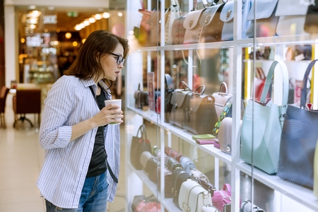 Adult woman looking at the showcase with bags and accessories in the shopping mall.