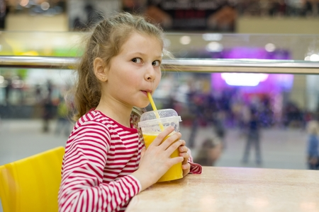 Girl child drinking juice in cafe, background shopping mall entertainment center. Lifestyle, leisure and people concept.