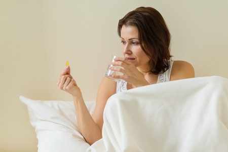 Woman takes pill with omega-3 and holding a glass of fresh water in bed morning. Vitamin D, E, a fish oil capsules. Nutrition, healthy eating, lifestyle