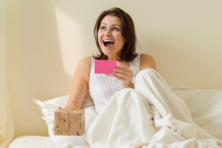 Middle aged woman in the morning in bed enjoys a gift. Reads card and happy Stock Photo