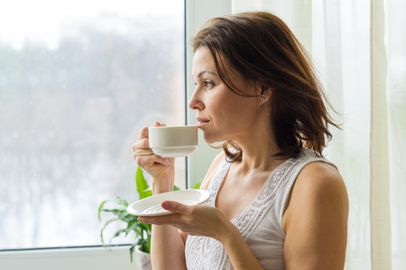 Mature woman drinks morning coffee and looks out the window at home. Photo in profile female serious.