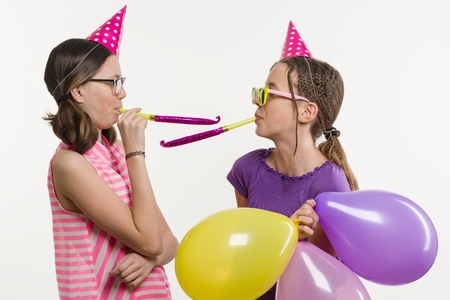 Teen girls at a party. Girls on a white background, in festive hats, blowing in the pipes