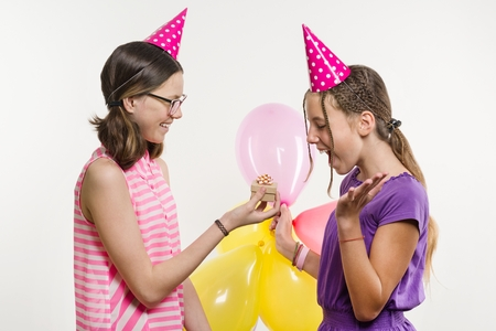 Birthday party. Girls teenagers give a gift. White background, in festive hats with balloons