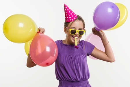 Cheerful teenage girl 12,13 years old, with balloons, in festive hat, blowing a pipe on white background
