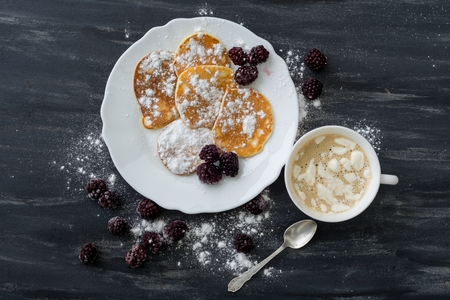 Tasty american pancakes with blackberries, powdered sugar, coffee with marshmallow. Top View.