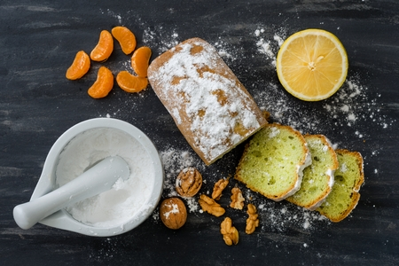 Mint cake sprinkled with powdered sugar on dark surface with fresh oranges mandarins.