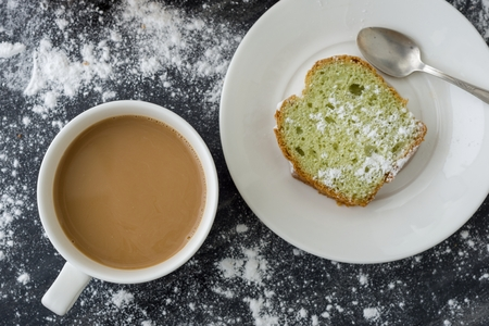Mint cake sprinkled with powdered sugar on dark surface with coffee cup, top view.