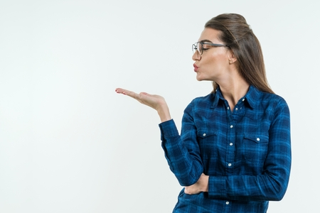 Young positive woman sends air sweet kiss. Snapshot in profile, on white background