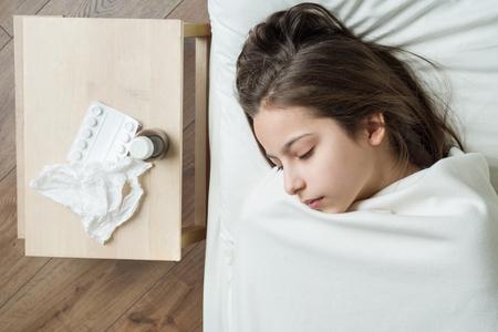 Cold flu season. Sick girl child in bed, near bed medication napkin. Stock Photo