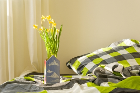 Spring yellow flowers in the interior of the bedroom. Stock Photo