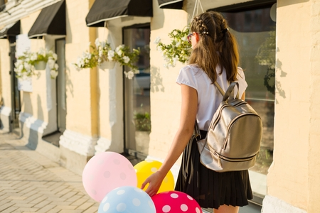 Back view. Girl teenager high school student with balloons, in school uniform goes along the city street. Stock Photo