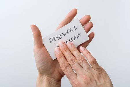 De hand van de vrouw houdt een wachtwoord op papier, dat het wachtwoord met vinger bedekt.