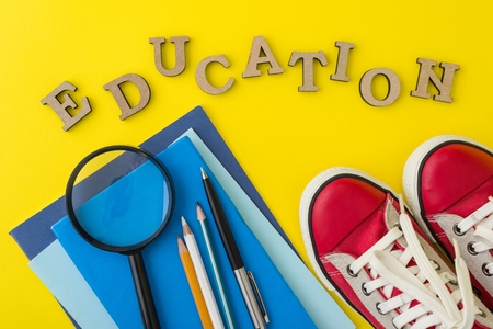 The concept of education. Red sneakers, school supplies, books, notebooks with yellow background. Stock Photo