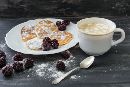 Tasty american pancakes with blackberries, powdered sugar, coffee with marshmallow. Top View