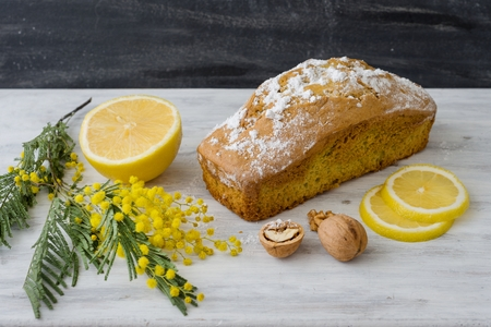 Lemon cake with nuts on a wooden white surface, a twig of mimosa flowers Stock Photo