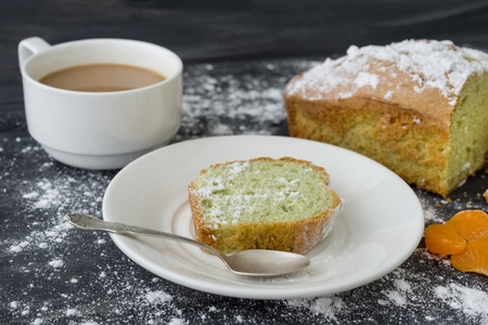 Mint cake sprinkled with powdered sugar on dark surface with coffee cup.